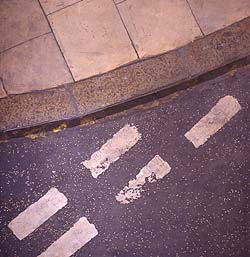 An incredibly detailed and realistic  of a street corner. At the top is a curve of kerb and pavement. At the bottom, tarmac with road markings in white paint